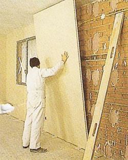 Instalador presentando un panel de pladur