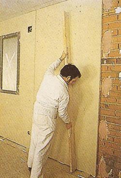 Instalador nivelando un panel de pladur
